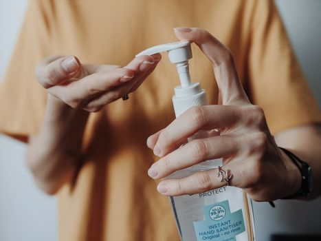 Canva - Woman pumping hand sanitizer from a bottle.jpg